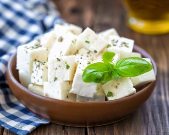 кусочки сыра фета с зеленью в тарелке