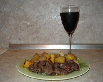 косуля с картошкой запеченная в духовке и поданная на стол с бокалом вина