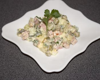 оливье с вареной колбасой и свежими огурцами в белой тарелке на столе