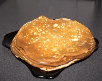 стопочка бабушкиных блинов в тарелке на кухонном столе