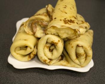 начиненные заварным кремом блинчики, сложенные горкой в тарелке