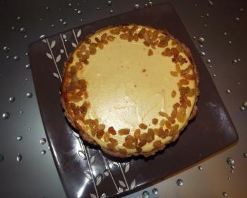 чизкейк из творога, украшенный изюмом, в квадратной тарелке на кухонном столе