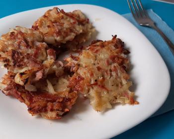 драники с колбасой в белой тарелке на кухонном столе