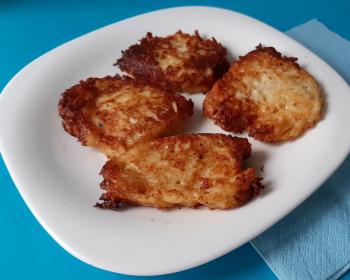 четыре картофельных драника с сыром в тарелке на столе