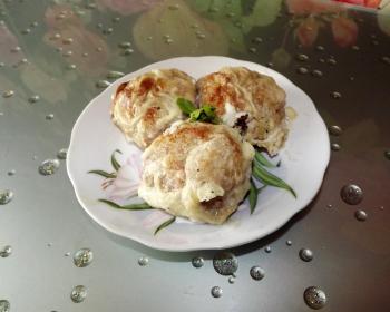три фрикадельки в сметанном соусе в тарелке на столе