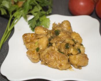 курица по-пекински в белой тарелке на столе, рядом свежая зелень