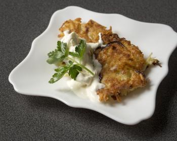 два латкеса в блюдце со сметаной и веточкой свежей петрушки
