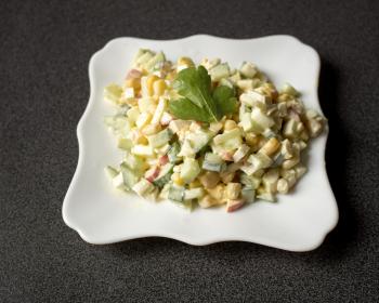 салат Нежность с крабовыми палочками в белой фигурной тарелке на столе