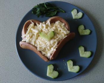 сосиска с яйцом в виде сердца на тарелке с огурцами