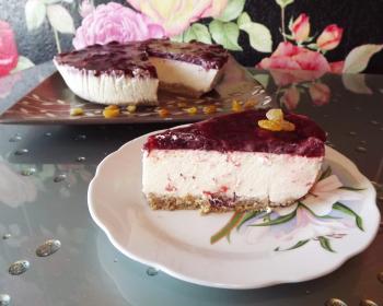 треугольный кусочек чизкейка без выпечки в блюдце на столе, на фоне оставшаяся часть десерта