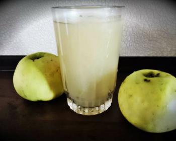 стакан яблочного киселя и два зеленых яблока рядом на столе