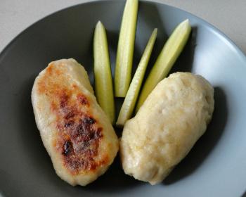 две куриных котлетки с яйцом внутри в тарелке с нарезанным огурцом