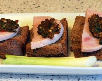 абхазская аджика, намазанная на три кусочка вареной колбасы, которые лежат на трех ломтиках черного хлеба на белой тарелке с зеленым луком на столе
