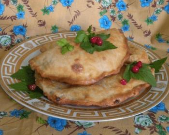 афарар с начинкой из творога и зелени на тарелке, несколько листьев петрушки и ягоды клюквы