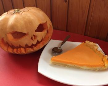 на белой тарелке лежит кусочек американского тыквенного пирога, рядом лежит чайная ложка, на столе, рядом с тарелкой лежит большая тыква в виде лица