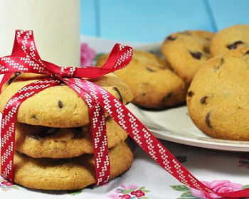 американское печенье с шоколадом лежит на тарелке, рядом стопкой сложены три печеньки, перевязанных лентой