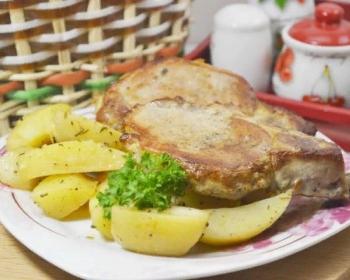 запеченный антрекот из свинины с кусочками картофеля и зеленью на белой плоской тарелке на столе