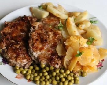 антрекот в тарелке с гариниром из консервированного горошка и жареного картофеля