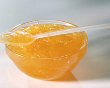 апельсиновый джем в стеклянной мисочке с чайной ложкой