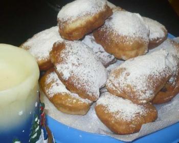армянские пончики, обильно присыпанные сахарной пудрой, в тарелке на салфетке, на фоне свеча