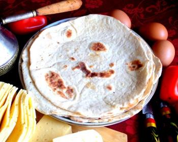 армянский лаваш, приготовленный на сковороде, на тарелке на столе, застеленном скатертью, рядом яйца, перец и нарезанный сыр