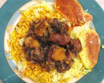 плов с кусочками мяса и сухофруктами на плоской тарелке на столе