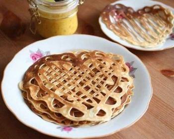 ажурные блинчики на белой тарелке с цветочками на столе