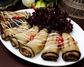тарелка баклажанных рулетиков бадриджани с майонезом, дополненные зернами граната и фиолетовыми листами салата