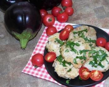 баклажаны с фаршем, пожаренные на сковороде в яичном кляре, присыпанные свежей зеленью, с помидорами черри на черной тарелке на салфетке, рядом на столе маленькие помидоры и круглые баклажаны