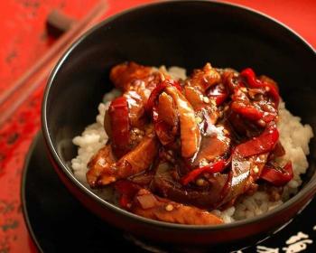 баклажаны с мясом по-китайски поверх вареного риса в пиале на столе