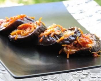 четыре маринованные кусочка баклажанов с морковью и чесноком на черной плоской тарелке на столе