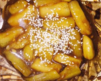 темная прозрачная тарелочка с баклажанами в кисло-сладком соусе, украшенными зернами кунжута