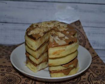 стопка банановых панкейков с вырезанным треугольным кусочком, политая шоколадом и посыпанная миндальными лепестками, на тарелке на столе, застеленном тканевой салфеткой