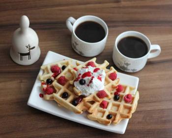 бельгийские вафли, поданые с мороженым, ягодами и вареньем, две чашки кофе рядом на столе