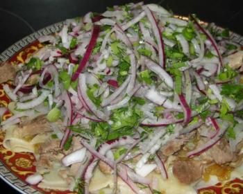 бешбармак из баранины в тарелке с обилием красного лука и зелени