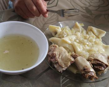 вареные пласты теста с жареным репчатым луком и кусочками мяса в стеклянной тарелке, бульон в белой миске на столе, застеленном скатертью