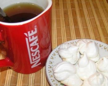 несколько кусочков безе на белой плоской тарелке на столе, покрытом деревянным ковриком, рядом чашка с чаем
