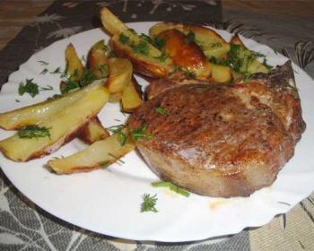 бифштекс из свинины в тарелке с запеченной картошкой