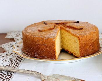 разрезанный сметанный бисквит на тарелке, стоящей на столе, застеленном ажурной белой салфеткой