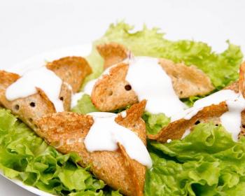 в тарелке на листьях салата лежат треугольные блинчики катаеф с грибами и сыром, сверху изделия политы сметаной