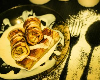 три блина, фаршированные печенью, выложенные друг на друга, на плоской тарелке на столе, присыпанном мукой