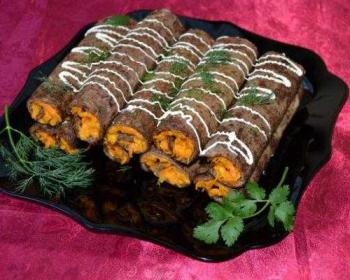 печеночные блины, свернутые рулетиками и начиненные морковью, политые майонезом и украшенные зеленью на тарелке на столе, застеленном тканевой скатертью