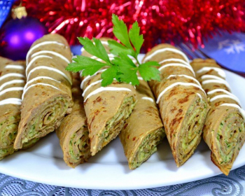 блины из говяжьей печени, свернутые рулетом с начинкой внутри, украшенные зелеными листиками, на белой плоской тарелке на столе