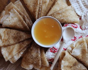блины на манке и молоке, свернутые треугольниками, разложены вокруг пиалы с медом