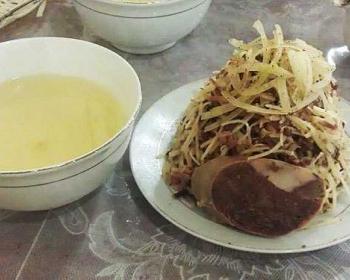 на тарелке лежит блюдо нарын с говядиной, рядом лежит кусочек конины, рядом с тарелкой стоит пиала с мясным бульоном