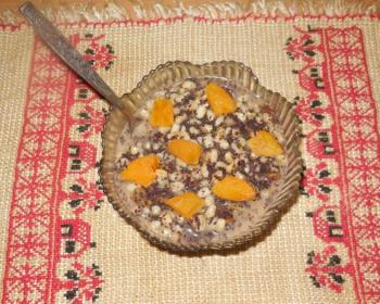 богатая кутья с маком, сухофруктами, пшеницей и орехами в стеклянной пиале с ложкой на столе, застеленном полотенцем