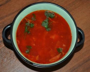 красный борщ с кусочками свинины, веточками петрушки и белокочанной капустой в белой кастрюле на столе