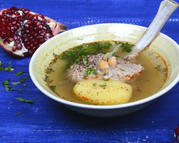 тарелка с бозбашем из баранины на кости с картофелем и зеленью, стоящая на синем столе, очищенный гранат на фоне