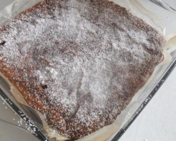 шоколадный брауни с орехами, присыпанный сахарной пудрой, в форме, застеленной пергаментом