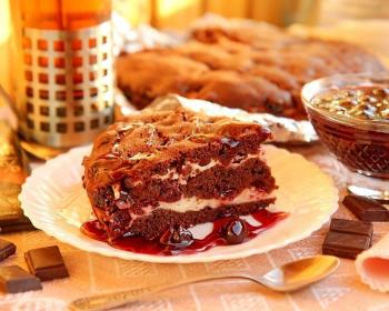 кусочек брауни с творогом и вишней, политый вареньем, на белой плоской тарелке на столе, застеленном скатертью, рядом чашка, пиала с вареньем и ложка